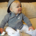 Baby wearing hooded top on sofa